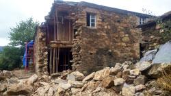 Vivienda en piedra con muro derrumbado